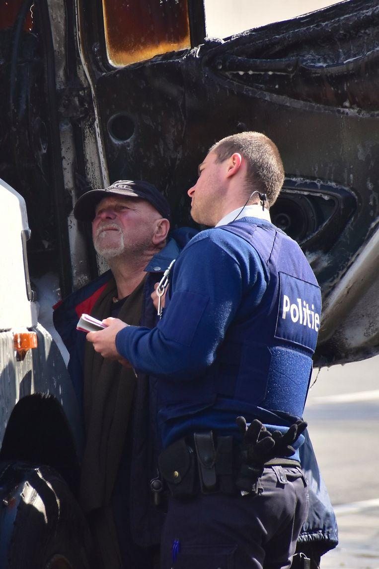 Bestuurder Willy Coussement bekijkt samen met een politieman de schade aan de binnenzijde van de trekker.