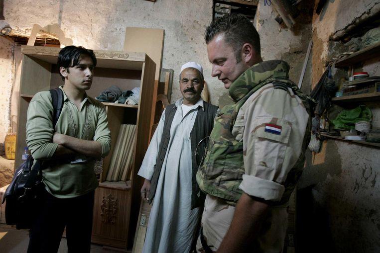 Een Nederlandse militair onderhandelt via een tolk (links) met een Afghaanse timmerman. Beeld anp