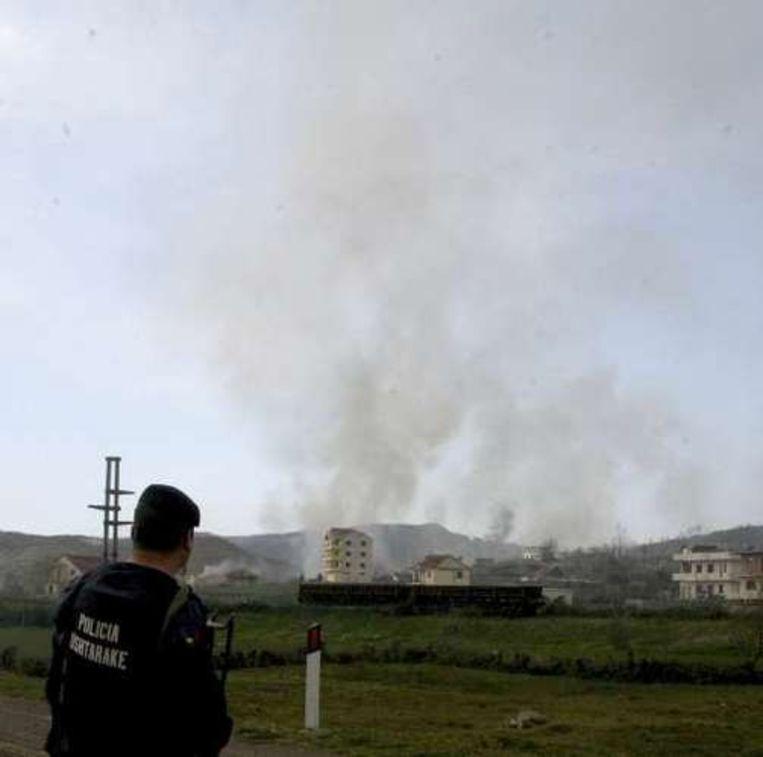 In de verte stijgen ruikpluimen op na de explosies.