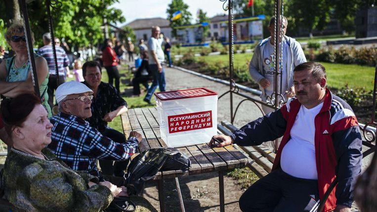 Inwoners van Svatove bij een lokaal 'mobiel stembureau'. Beeld afp