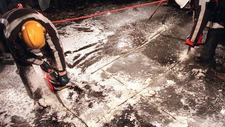 Brandweermannen zagen op 28 januari 1996 in het Friese Balk stukken ijs uit het zogenoemde zwaaigat, waar in de zomer boten draaien. Het ijs dat 25 centimeter dik is werd naar een wak onder de Raadhuisbrug gebracht, een van de knelpunten in het parcours van de Elfstedentocht. © ANP Beeld