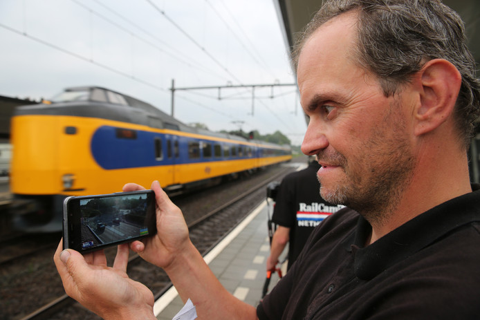 Pascal Esselink op het station in Twello kijkt op zijn telefoon via de webcam naar de spoorwegovergang in Helmond. Wessel van Zuiden staat op de achtergrond.