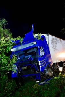 Truck rijdt bomen uit de grond en belandt in de sloot in Oeffelt