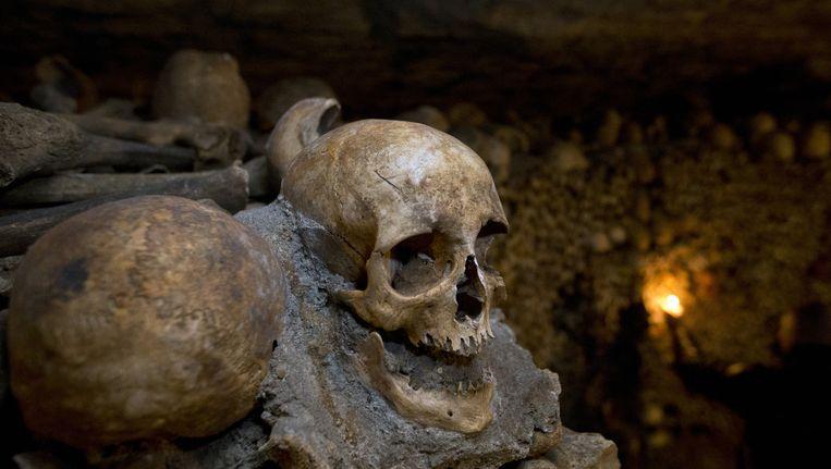 In de Parijse catacomben liggen miljoenen doodshoofden en skeletten op elkaar gestapeld. Beeld ap