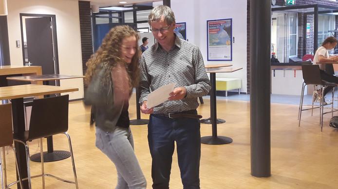 Kristel van den Boom uit Heeswijk-Dinther is verheugd want ze is geslaagd. Conrector Hans Manders van Gymnasium Bernrode laat haar haar cijferlijst zien en feliciteert haar.