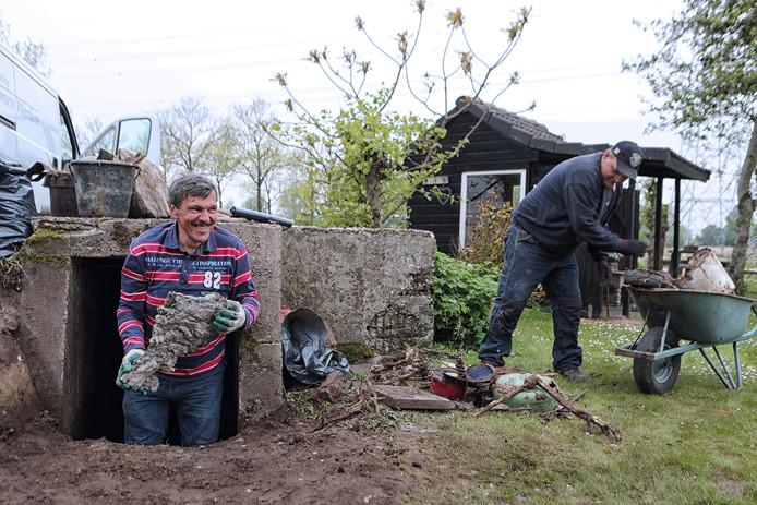 John van Tilburg (l) en Peet Letcher hebben letterlijk hun handen vol aan het leegruimen van de bunker achter het huis van de familie Groenveld.