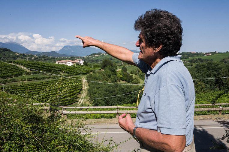 Gianluigi Salvador laat de wijngaard van zijn buren zien. Beeld Nicola Zolin