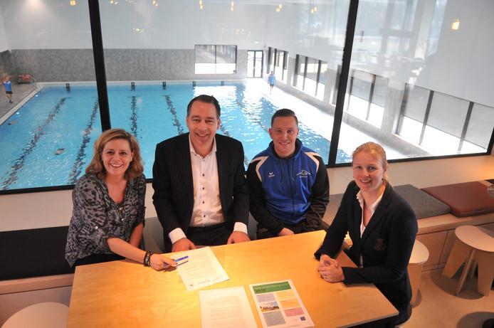 Mirjam Jager (zwembad Oosterbeek), wethouder Jasper Verstand, Tim van Guilik (sportbureau) en Sabine Boshuis (zwembad Doelum) tekenen de nieuwe overeenkomst rondom het schoolzwemmen in Renkum.