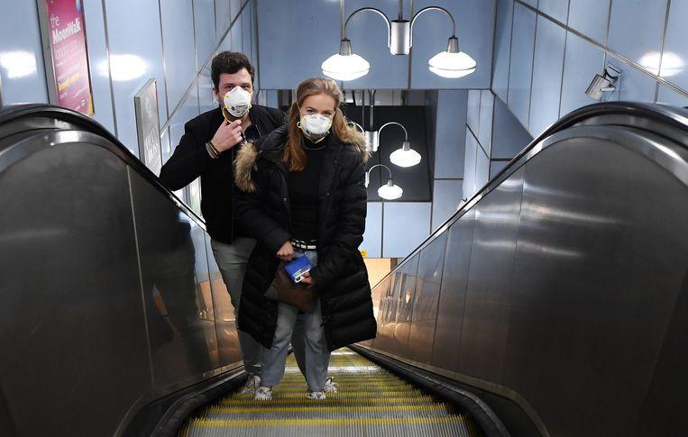 Een koppel met gezichtsmaskers in de Underground in Londen. Beeld EPA