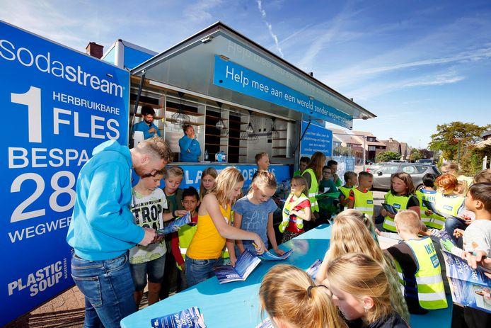 Berry Kolen van SodaStream helpt de leerlingen bij de Plastic Soup Bus met het vinden van de juiste antwoorden.