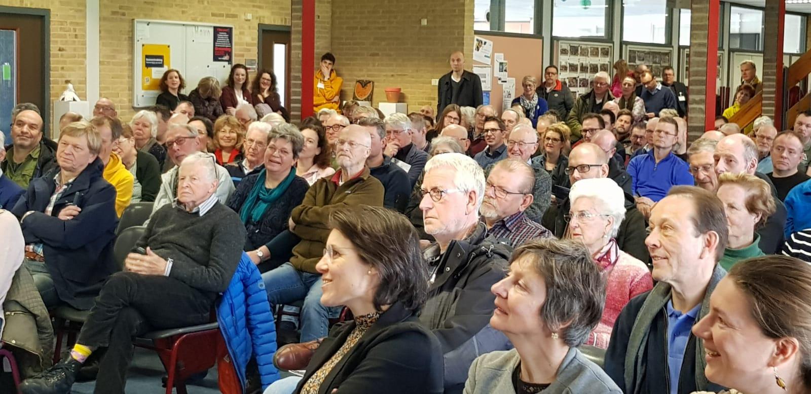 Inwoners van Schothorst-Zuid luisteren op 7 maart met belangstelling naar de plannen voor een warmtenet in hun wijk. Op de voorgrond in het midden verantwoordelijk wethouder Astrid Janssen.