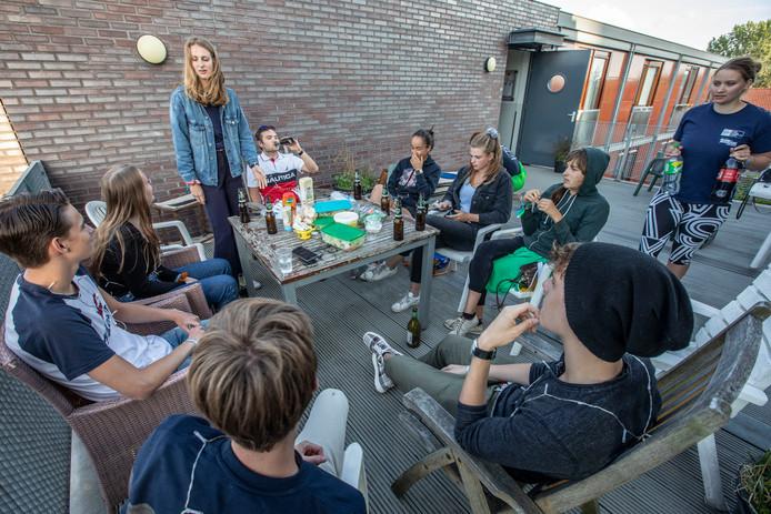 Studenten Bouwkunde eten bij hun 'intro-ouders' Annemieke van Harten en Tessa van Amelsvoort (staand).