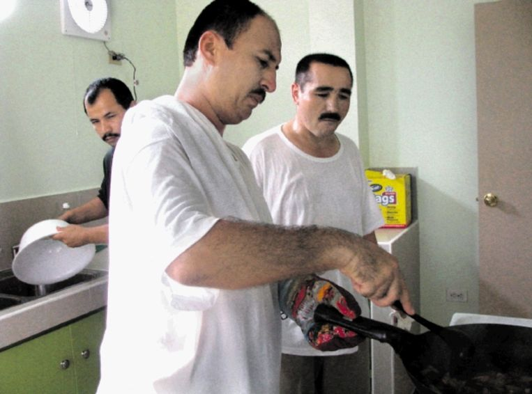 Drie van de zes door Palau opgenomen Oeigoeren in de keuken van hun nieuwe onderkomen. (FOTO AFP) Beeld