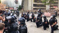 Agenten knielen tijdens protesten om hun solidariteit te tonen