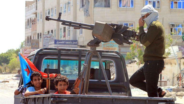 Jemenitische kindsoldaten aan de kant van het regeringsleger met geweren in een zwaar bewapende pick-up truck. Beeld AFP