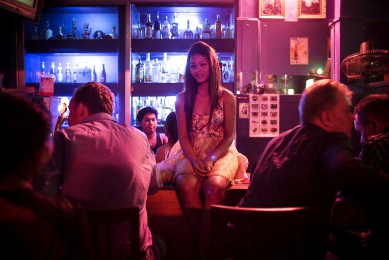 Een prostituee zit op de bar in een nachtclub in Phnom Penh, Cambodja. Beeld Julius Schrank