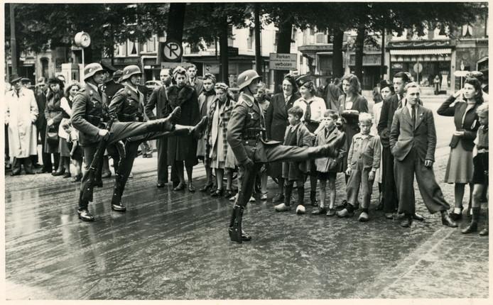Hagenezen kijken toe als Duitse soldaten over het Plein marcheren.