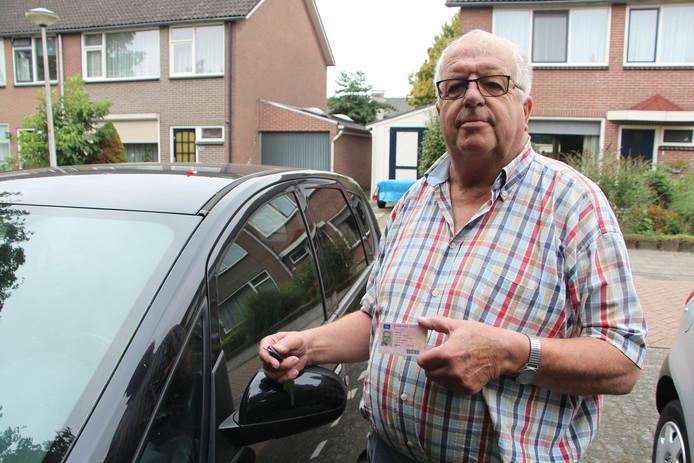 Borculo - Jos Vaalt (75) met zijn inmiddels verlopen rijbewijs bij zijn auto. Hij laat zich zonodig rijden, stapt zelf niet achter het stuur zolang het CBR niet opschiet om hem aan een nieuw geldig rijbewijs te helpen.