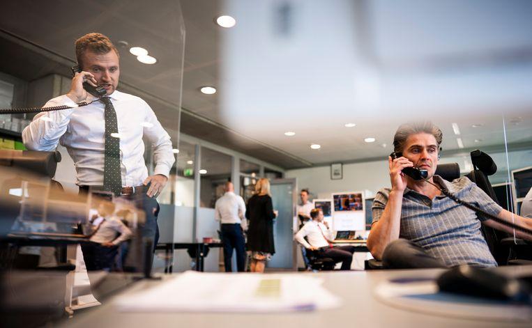 Ambtenaren aan de telefoon in de dealingroom van het Ministerie van Financiën. Beeld Freek van den Bergh / de Volkskrant