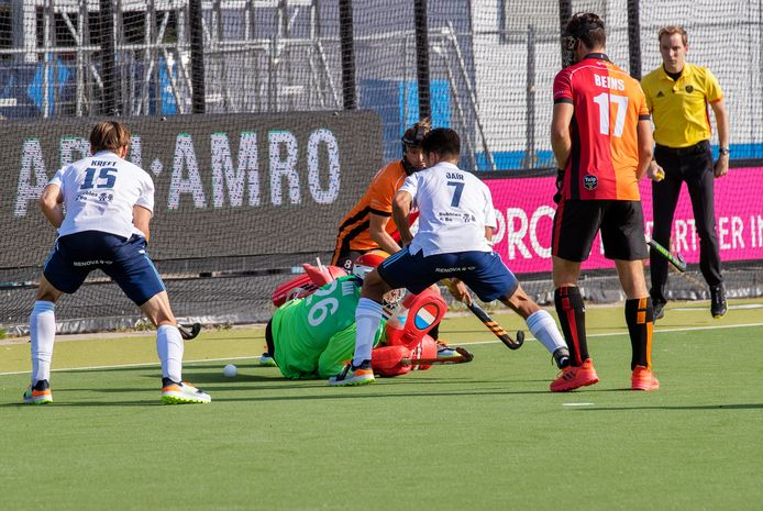Jair van der Horst van HC Tilburg en Oranje-Rood-speler Teun Beins kijken toe hoe na een strafcorner de bal onder Oranje-Rood-goalie Primin Blaak doorgaat.