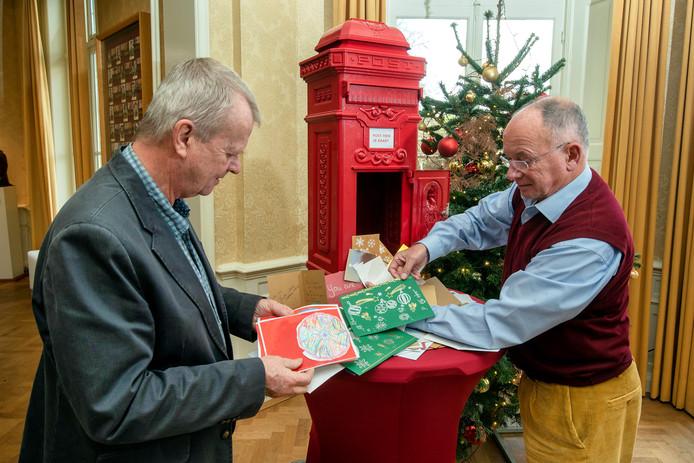 Frans Ammerlaan (l) en Roger Beets bekijken de oogst aan kerstkaarten voor de oorlogsveteranen in december vorig jaar.