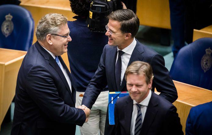 Rutte, hier met 50Plus-leider Henk Krol, schudt handen voorafgaand aan het debat.