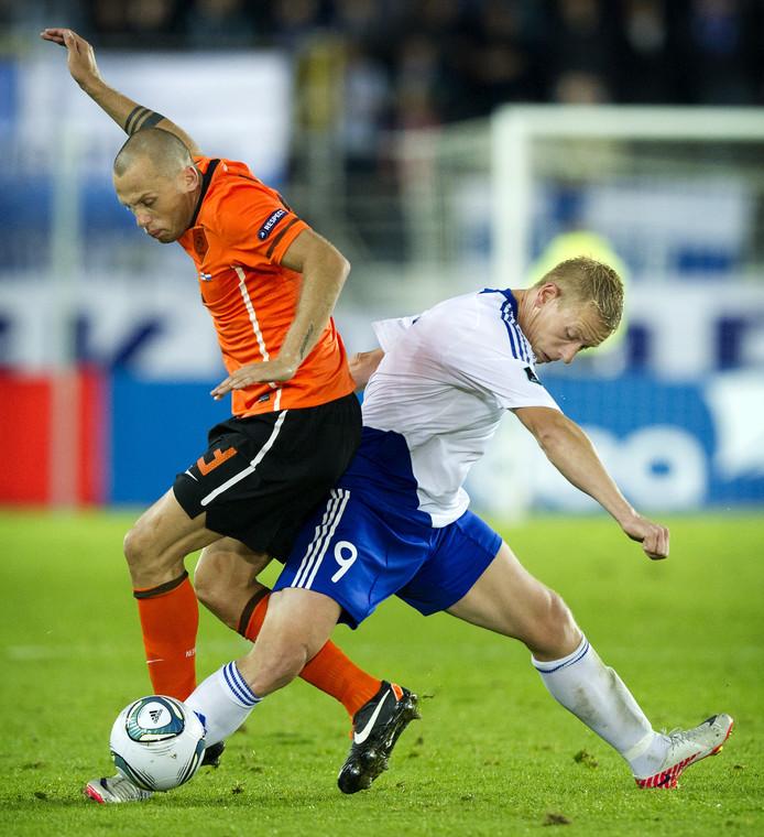 John Heitinga (L) in duel met Mikael Forssell van Finland tijdens de EK kwalificatiewedstrijd tegen Finland in het Olympisch stadion van Helsinki.