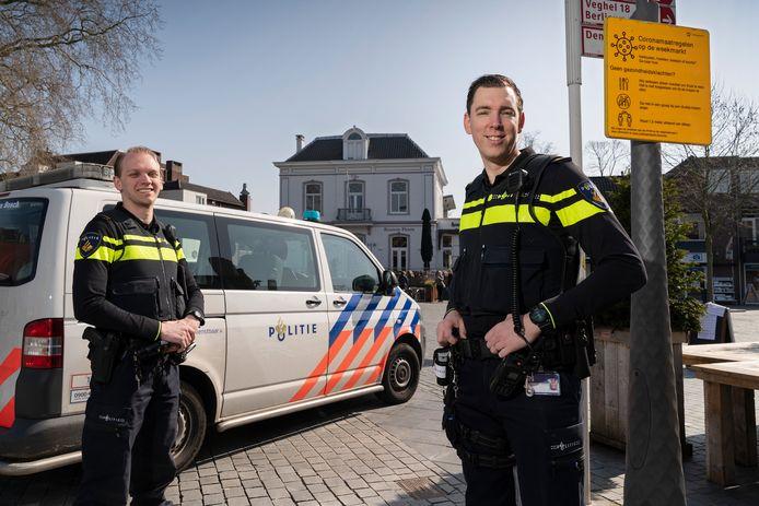 Agenten Bart Gallé (links) en Roy Peijnenburg in het centrum van Rosmalen. Naast Peijnenburg hangt een bord met coronamaatregelen, en die worden vooralsnog vrij goed nageleefd.
