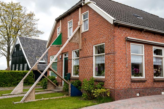 Een beschadigde woning wordt versterkt met stutten, foto ter illustratie