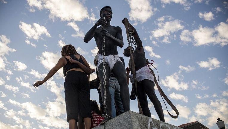 Zuid-Afrikaanse studenten op de sokkel waarvandaan ze zojuist het beeld van Cecil Rhodes hebben verwijderd Beeld getty