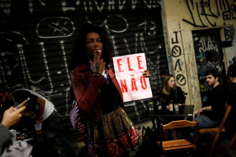 Een vrouw met het teken van 'Niet Hij' tijdens de demonstratie in São Paulo.  Beeld REUTERS