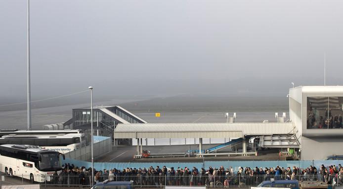 Lange rijen reizigers wachten op de bussen op Eindhoven Airport.