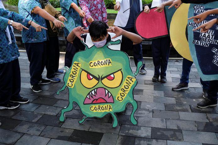 Studenten in Indonesië hebben van de angst voor het virus straattheater gemaakt.