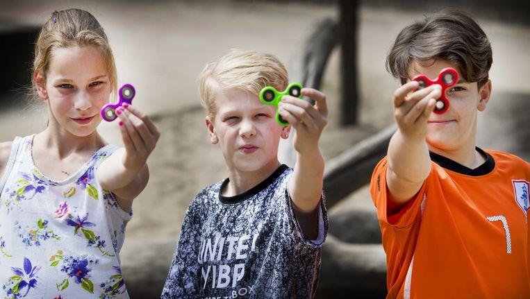 Scholieren spelen met een fidget spinner, een klein tolletje dat je moet laten draaien tussen duim en wijsvinger. Het speeltje zou kinderen met adhd helpen te ontspannen. Beeld anp