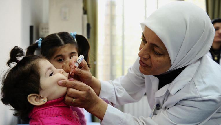 Een werknemer van UNICEF dient een Syrisch kind in de hoofdstad Damascus een vaccinatie toe voor polio. Beeld ap