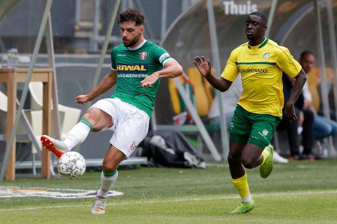 Kursad Sürmeli van FC Dordrecht wordt tijdens een oefenduel op de huid gezeten door Bassala Sambou van Fortuna Sittard.