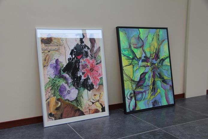 De twee schilderijen staan klaar om opgehangen te worden.