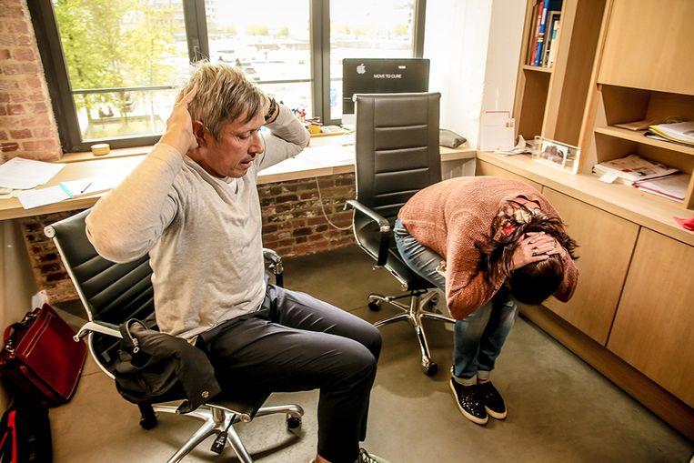 Oefening aan je bureau: Vouw je handen achter je hoofd, zet je voeten plat op de grond, buig je hoofd en probeer met je neus je knieën te raken