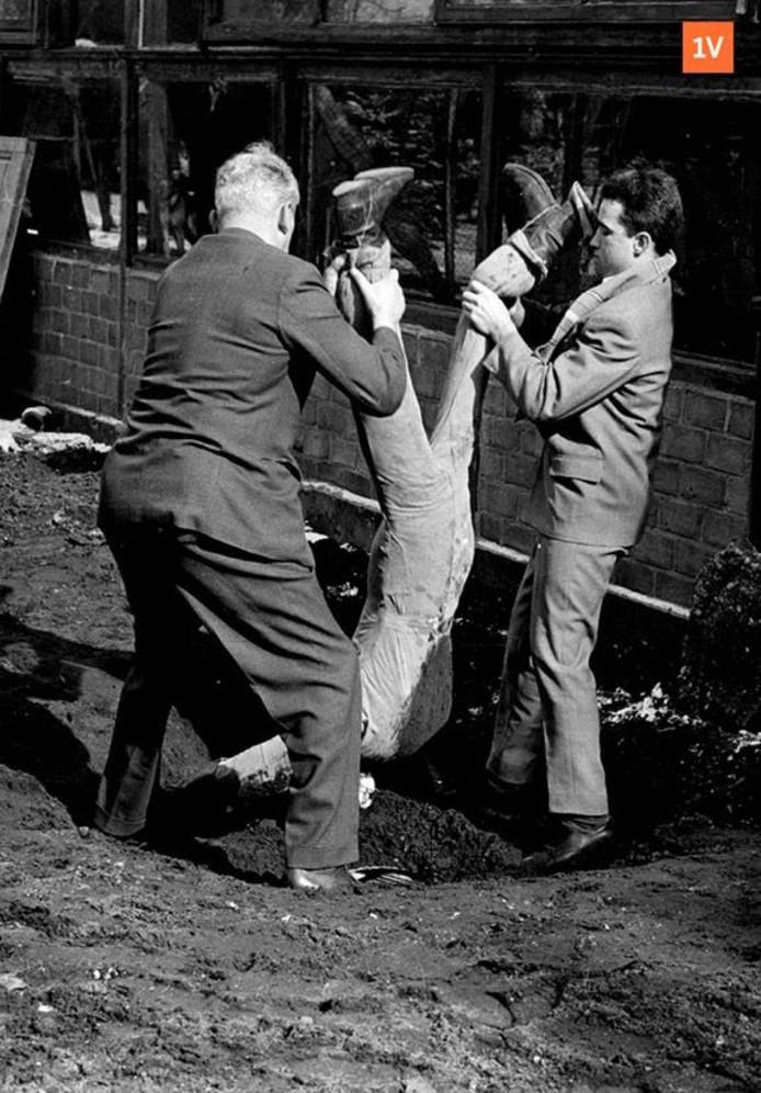 Politieacteurs hangen een pop boven een put. 'De 14-jarige Theo hangt levenloos op zijn kop tussen zijn twee vrienden, boven de waterput', is het originele bijschrift.