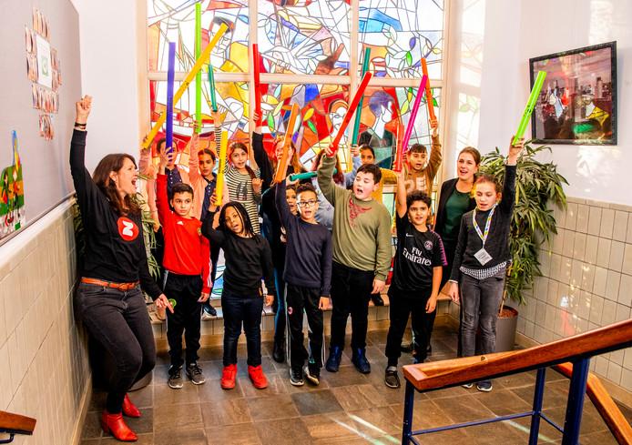 Initiatiefnemer Melissa 't Hart zingt een liedje met een vrolijke klas kinderen.