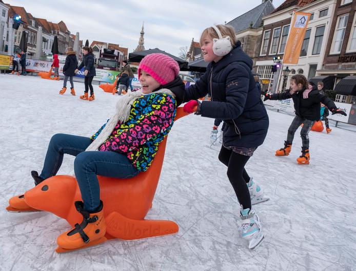 De 8-jarige meiden Evi Pol (staand) en Noor Vermunt (zittend) hebben de grootste lol op de schaatsbaan in Zierikzee.