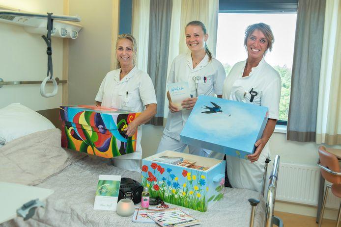 Verpleegkundige Astrid Cornelissen (rechts) ontvangt met collega's de waakkoffers in Gelre Apeldoorn.