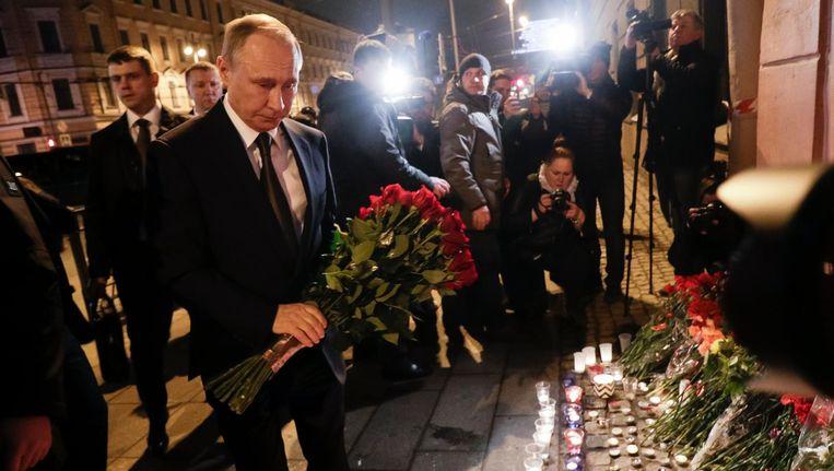 President Poetin legt bloemen bij het getroffen station. Beeld AP