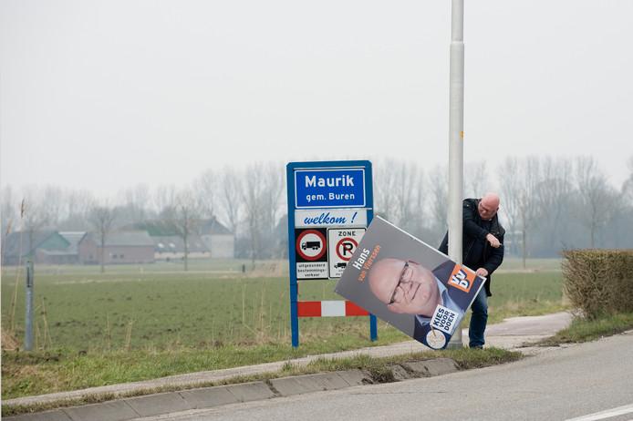 Tafereel uit de verkiezingscampagne: VVD'er Hans van Vierssen moet in Maurik zijn sandwichbord verwijderen op last van de gemeente.