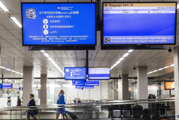 Een waarschuwing voor het coronavirus in de aankomsthal van Schiphol.  Beeld ANP