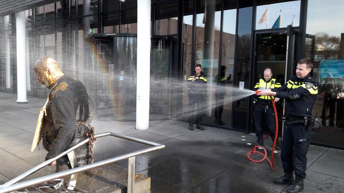 Een protestactie van Arie den Dekker op dinsdag 29 januari: hij ketende zich vast voor het gemeentehuis van Oss en bedekte zich met koeienstront. De politie spoot hem schoon.