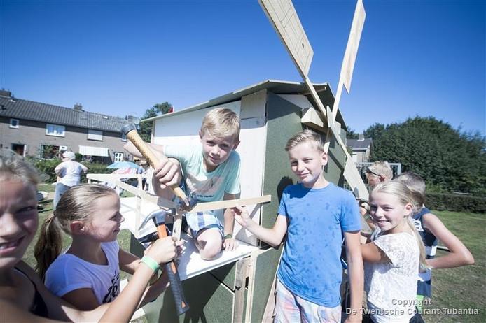 Jongens poseren trots bij hun bouwwerk op Houtdorp.