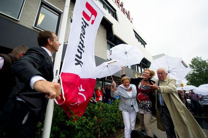 Bertus Heutink (rechts) hijst met dochter Jessica (naast hem) en schoonzoon Henk Fokke de vlag in top van het 100-jarige Heutink Onderwijs.