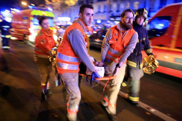 Een vrouw wordt geëvacueerd uit concertzaal Bataclan.