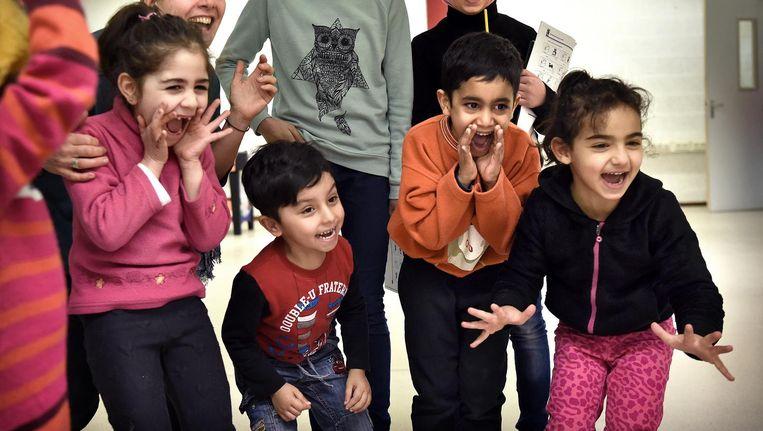 Kinderen uit noodopvang Heumensoord spelen op een school in Nijmegen. Beeld Marcel van den Bergh / de Volkskrant